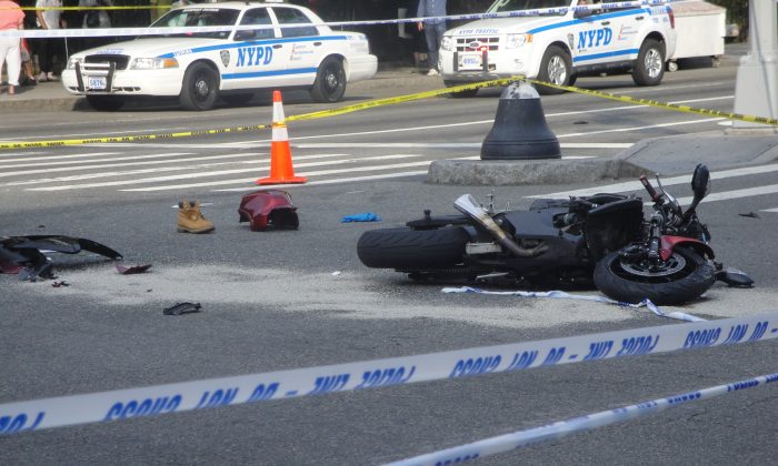 A motorcycle and the driver's shoe are seen in the street after it hit a minivan at the intersection of West Houston and LaGuardia Place on Aug. 21. The motorcyclist was pronounced dead on the scene. (Sarah Matheson/Epoch Times)