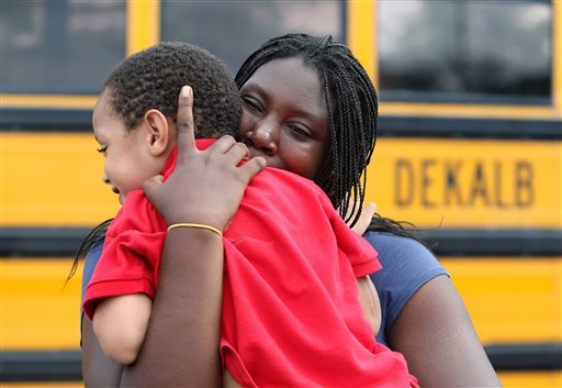 LaTrease Akins hugs her 5-year-old son Mark Wheeler after being reunited following a shooting incident at McNair Discovery Learning Academy Tuesday, Aug. 20, 2013 in Decatur, Ga. A teen opened fire with an assault rifle Tuesday at officers who shot back at the Atlanta-area elementary school, the police chief said, with dramatic overhead television footage capturing the young students racing out of the building, being escorted by teachers and police to safety. No one was injured. (AP Photo/Atlanta Journal-Constitution, Ben Gray)