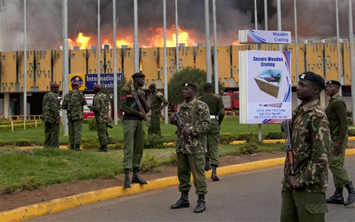 Armed policemen cordon off the area as fire rages at the international arrivals unit of Jomo Kenyatta International Airport, Nairobi, Kenya, Wednesday, Aug. 7, 2013. A massive fire engulfed the arrivals hall at Kenya's main international airport early Wednesday, forcing East Africa's largest airport to close and the rerouting of all inbound flights. Dark black smoke that billowed skyward was visible across much of Nairobi as emergency teams battled the blaze. (AP Photo/Sayyid Azim)
