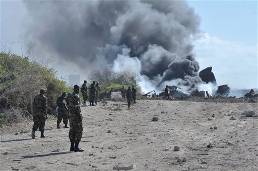 In this handout photo released by African Union Mission in Somalia (AMISOM), AMISOM soldiers look on as a plane burns on the runway at the site of an airplane crash in Mogadishu, Somalia, Friday, Aug. 9. 2013. An Ethiopian Air Force aircraft crashed upon landing this morning at Mogadishu's Aden Adde International Airport. Two of the six crew members survived the crash. (AP Photo/Tobin Jones, AU/UN IST, AMISOM)