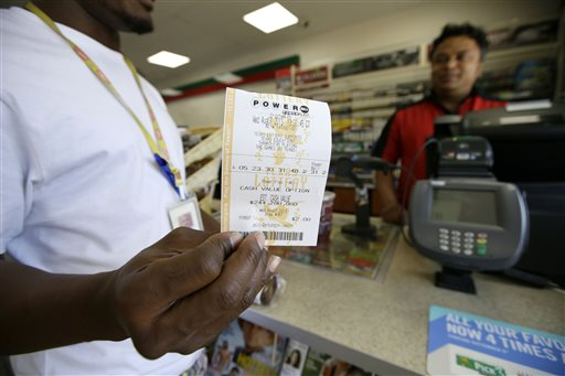 Raj Prasai, right, watches after making a sale to Eric, left, who did not want to give his last name in case he won the Powerball Jackpot, holds what he said would be the winning numbers after making the purchase, Wednesday, Aug. 7, 2013, in Dallas. The Powerball jackpot is expected to be about $425 million by Wednesday's drawing, making it the game's third largest ever.(AP Photo/Tony Gutierrez)
