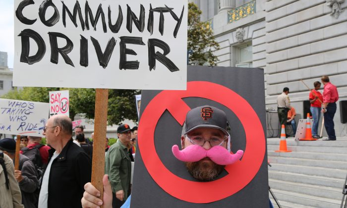 A protestor demanding an end to ride-sharing services at San Francisco City Hall, Calif., July 30, 2013. (Christian Watjen/Epoch Times)