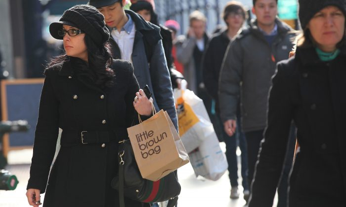People carry shopping bags on Broadway in Manhattan, New York City. To encourage New Yorkers to reuse bags, City Council is proposing a 10 cent surcharge on bags at grocery and retail stores. (Mario Tama/Getty Images)