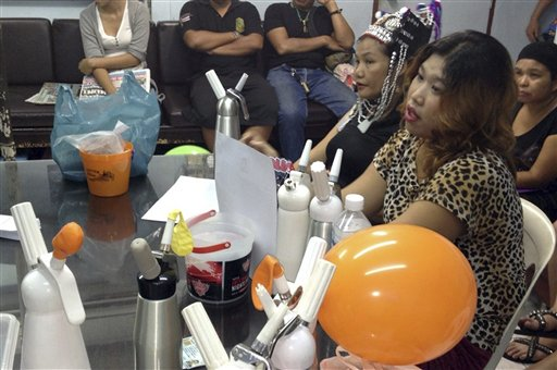 In this photo taken August 24, 2013, Thai vendors, right, are shown at a police news conference with laughing gas balloons, foreground, following their arrest in Bangkok, Thailand. Thai authorities are cracking down on vendors in Bangkok's main backpacker district selling cheap doses of balloons filled with nitrous oxide, or laughing gas, to tourists. (AP Photo/Daily News)