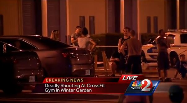 In this screenshot of video from WESH-TV, police officers question witnesses at the scene of a shooting at CrossFit Mosaic Gym in Winter Garden, Florida on August 12, 2013. The owner of the gym, Richard Millsap, was shot and killed. (Screenshot/WESH-TV)