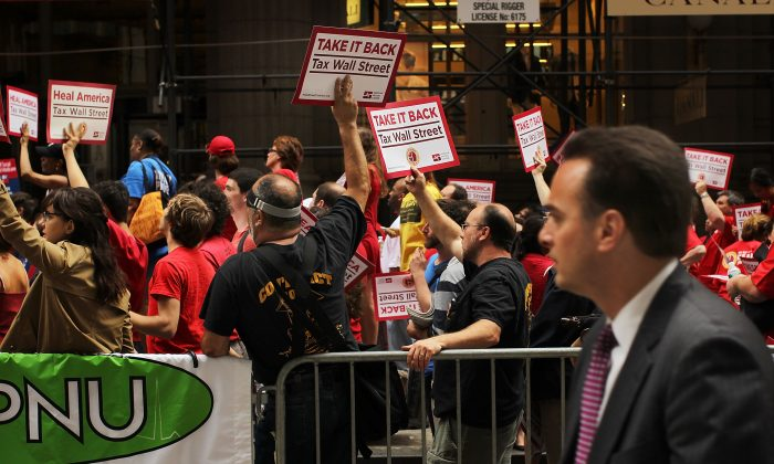 A businessman walks by members of the nurses union and other workers protesting income inequality on Wall Street, June 22, 2011. (Spencer Platt/Getty Images)