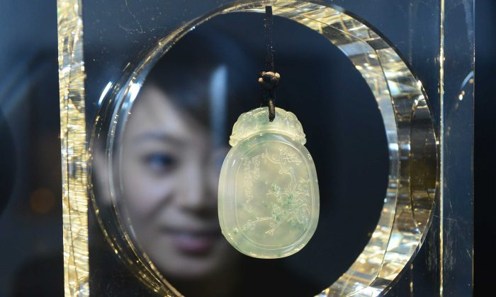 Awoman looking at a piece of jewelry at the China International Jewellery Show in Beijing, Dec. 16, 2012.  (STR/AFP/Getty Images)
