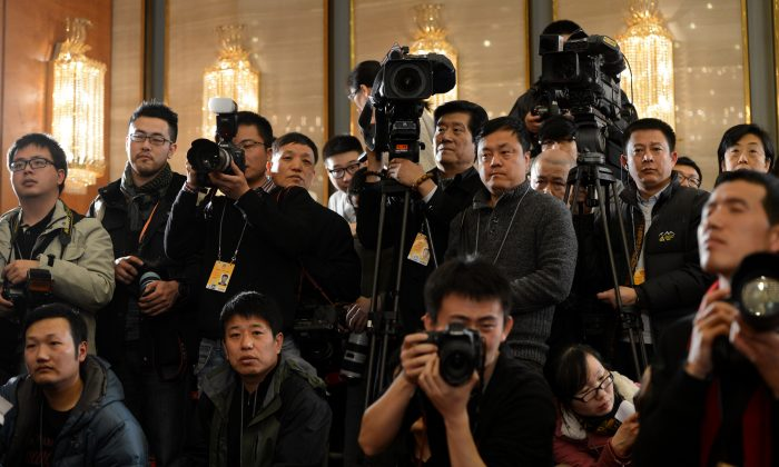 Chinese journalists cover the Chinese People's Political Consultative Conference (CPPCC) press conference at the Great Hall of the People in Beijing on March 2, 2013. According to China analyst He Qinglian, the Chinese Communist Party ensures that the news in China is always reported from the CCP's viewpoint. (Mark Ralston/AFP/Getty Images)
