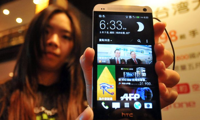 A staff member displays Taiwanese smartphone maker HTC's new 'HTC One' during a press conference in Taipei on Mar. 7, 2013. An HTC executive, Chien Chih-lin, was arrested on Aug. 31 for allegedly leaking trade secrets to mainland Chinese firms. (Mandy Cheng/AFP/Getty Images)