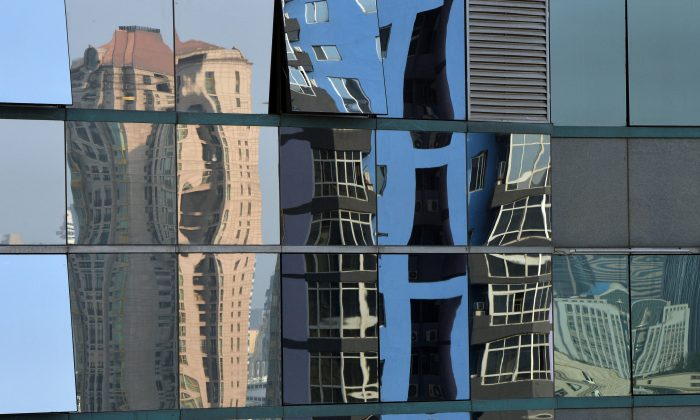 High rise properties are reflected on an office building's windows in Beijing on May 6, 2013. Home prices in Beijing continue to rise, in spite of the awareness that the housing bubble in China will eventually burst. (Mark Ralston/AFP/Getty Images)