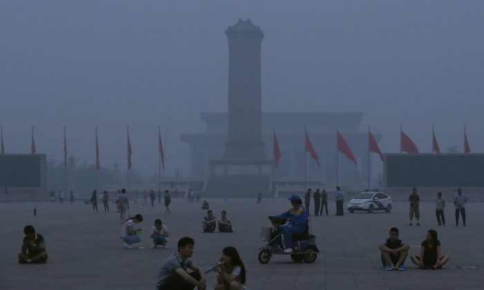 Chinese tourists wait for watching the customary ceremony of lowering flag on the Tiananmen Square at dangerous levels of air pollution on June 28, 2013 in Beijing, China. Nosebleeds, possibly linked to high pollution levels, were reported recently in a Zhejiang elementary school. (Feng Li/Getty Images)