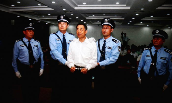 A screen shows the picture of the sentencing of disgraced former Politburo member Bo Xilai (Center) on Sept. 22, 2013 in the Jinan Intermediate People's Court, in Shandong Province, China. Chen Pokong argues Bo's trial was used by Party central to attack two other high-ranking officials. (Feng Li/Getty Images)