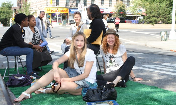 Aleksandra Bielska (L), and her friend Beata Frankowicz(R), who are visiting New York from Poland, are camping out on the tuft set up by the Montefiori Park Neighborhood Association on 138th Street and Broadway, Sept. 20, 2013. This day marks the international Park(ing) Day initiative, celebrated in 162 cities around the world. (Kristina Skorbach/Epoch Times)