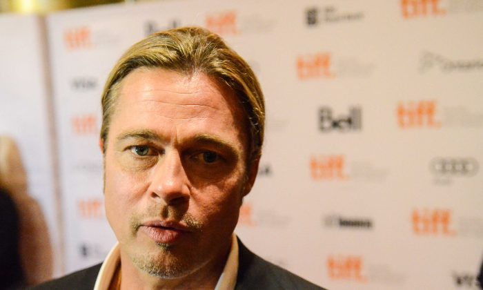 """Actor Brad Pitt walks down the red carpet for the premiere of """"12 Years a Slave"""" on Sept. 6, 2013. Pitt, who has an important cameo in the film and helped to secure funding, said the story has a message that people need to hear. (Matthew Little/The Epoch Times)"""