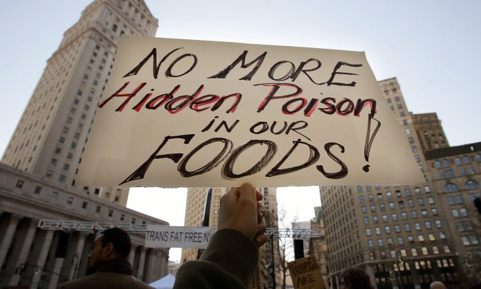 A protester holds a sign reading 'No More Hidden Poison in Our Foods' at a rally against trans fats Oct. 30, 2006, in New York City. (Mario Tama/Getty Images)