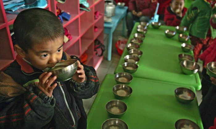 """Photo taken on Nov. 27, 2007, showing a child in Henan Province, where life in his village has returned to 1960s China, having rejected market reforms and returned to a collective economy with villagers working for the good of the community. A communist official in western China has apparently laid claim to fathering half the children in his village with """"left behind"""" wives whose husbands have to go to cities to get work. (Peter Parks/AFP/Getty Images)"""