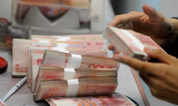 In this file photo, Chinese 100-yuan notes are counted at a bank in Shanghai on April 11, 2008. According to Cheng Xiaonong, hot money—money moving into China seeking a short-term profit—accounts for 10 percent of China's GDP. (Mark Ralston/AFP/Getty Images)
