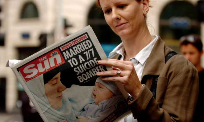 "A woman holds a copy of the British tabloid newspaper The Sun, in London, Friday, Sept. 23, 2005 which carries on its front page their story of Samantha Lewthwaite, who is pictured with her daughter Ruqayyah. There is speculation that the ""White Widow"" is behind the terror attack on Westgate mall in Nairobi, which started on September 21 and has killed at least 72 people while injuring over 150 others. (AP Photo/Andrew Stuart)"