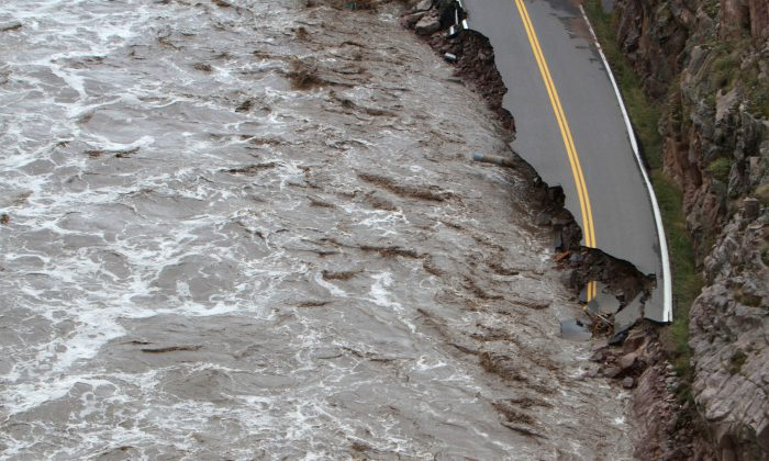 This aerial photo shows Highway 34 being destroyed toward Estes Park , Colo. as flooding continues to devastate the Colorado Front Range and thousands are forced to evacuate with an unconfirmed number of structures destroyed Friday, Sept. 13, 2013. (AP Photo/Colorado Heli-Ops, Dennis Pierce)