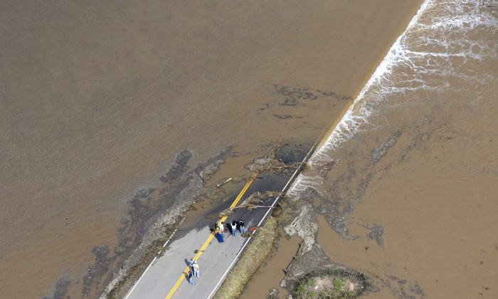 People stand at the edge of a highway washed out by flooding along the South Platte River in Weld County, Colorado near Greeley, Saturday, Sept. 14, 2013.  Hundreds of roads in the area have been damaged or destroyed by the floodwaters that have affected parts of a 4,500-square-mile area. (AP Photo/John Wark)
