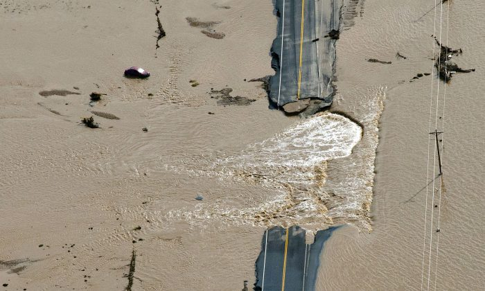 A section of highway washed out by flooding along the South Platte River in Weld County, Colorado near Greeley, Saturday, Sept. 14, 2013. (AP Photo/John Wark)