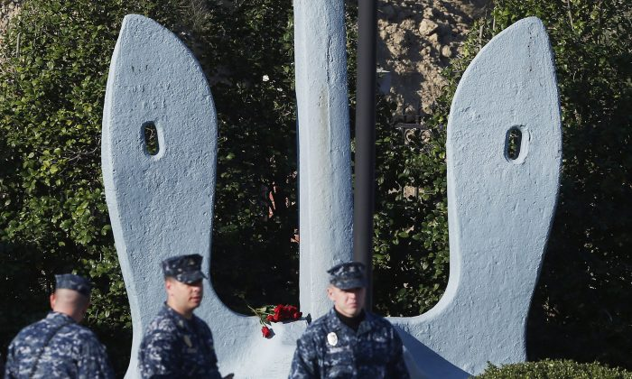 Roses that were placed on an anchor at an entrance of the Washington Navy Yard as security personnel stand watch, Sept. 19. The Washington Navy Yard began returning to near-normal operations three days after it was the scene of a mass shooting in which a gunman killed 12 people. (AP Photo/Charles Dharapak)