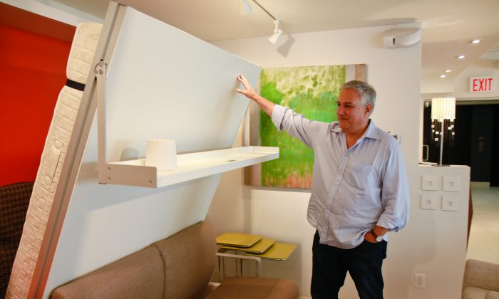 Ron Barth demonstrates a couch and shelf that folds down into a queen-sized bed at his Resource Furniture showroom in Manhattan. (Joshua Philipp/Epoch Times Staff)
