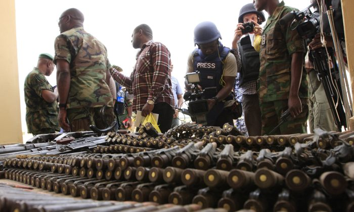 Journalists look at arms and ammunition which military commanders say they seized from Islamic fighters in Maiduguri, Nigeria, on Wednesday, June 5, 2013. Boko Haram, the radical group that once attacked only government institutions and security forces, is increasingly targeting civilians, as in a Sept. 29, 2013 attack on a College in Yobe State, Nigeria. (AP Photo/Jon Gambrell, File)