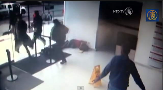 A security camera captures gunmen storming into a Colombia hospital to free a prisoner being seen by medical staff. (Screenshot/NTD Television)