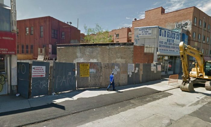 Wooden barriers surround a former construction site of Tommy Huang, in an image from Google Maps of Queens, New York City. Construction has been halted at the site where a worker was killed by a wall collapse in January 2011. (Screenshot/Google Maps)