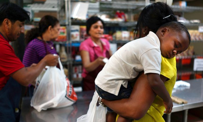 Jaden Painegua, 2, rests on his mother's shoulder at the West Side Campaign Against Hunger food bank on July 24, 2013, in New York City. The food bank assists thousands of qualifying New York residents by providing a monthly allotment of food. (Spencer Platt/Getty Images)