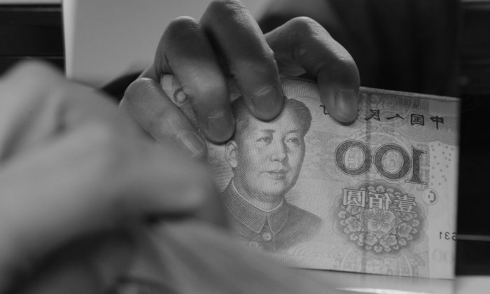 In this file photo a Chinese bank worker counts a stack of 100-yuan notes, on Feb. 27, 2011. According to a study done by the People's Bank of China, household savings rates in China now stand at 50 percent. (AFP/AFP/Getty Images)