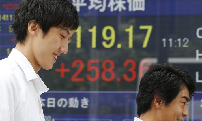 People walk by an electronic stock board in Tokyo, Japan, Sept. 9, 2013. (AP Photo/Koji Sasahara)
