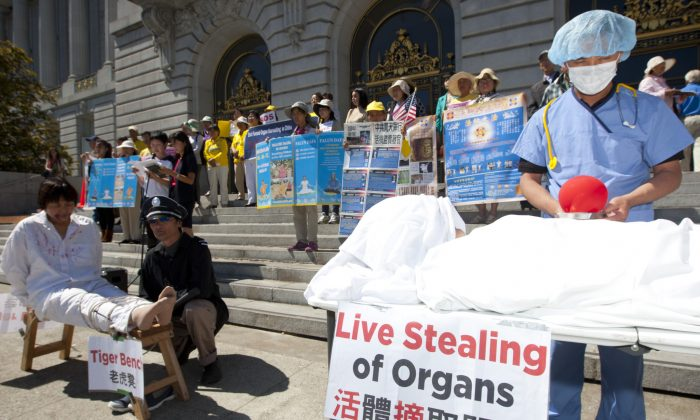 Actors re-enact organ harvesting and torture being done on Falun Gong practitioners, while demonstrators hold signs at a press conference to support House Resolution 281 against organ harvesting in China, at San Francisco City Hall, Sept. 5, 2013. (Epoch Times)