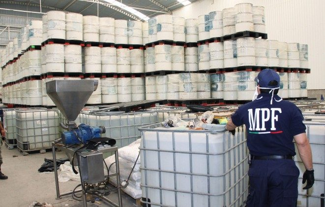 An officer from the Federal Public Ministry looks at drums of precursor chemicals for methamphetamine that were seized in Queretaro, Mexico, on June 20, 2011. (AP Photo/Attorney General's office, File)