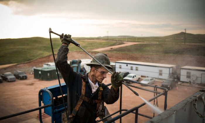 A worker on an oil rig drilling into the Bakken Shale formation on July 28, 2013, outside Watford City, N.D. (Andrew Burton/Getty Images)