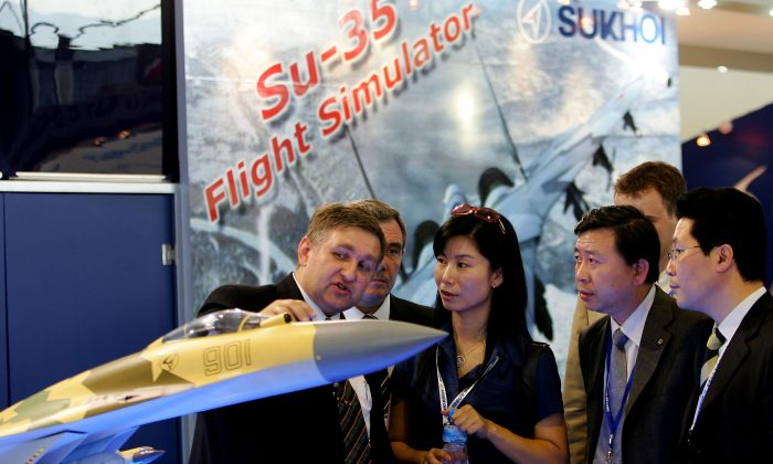 A man describes the Russian Su-35 fighter jet to Chinese visitors at Airshow China 2006 on Nov. 1, 2006 in Zhuhai, China. The Chinese regime is expected to sign a deal with the Russians to obtain the Su-35 next year. (Guang Niu/Getty Images)