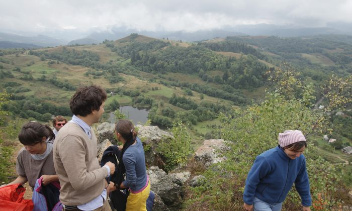 Hikers look out over the Corna Valley as they stand on Carnic mountain at the Rosia Montana gold mine site on Sept. 12 in Romania. Carnic mountain is one of four in the immediate area that are rich in gold and silver deposits, and that Rosia Montana Gold Corporation, which is majority-owned by the Canadian company Gabriel Resources, is seeking to exploit. (Sean Gallup/Getty Images)
