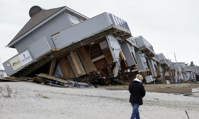 A woman walks past a cabana complex on the beach pulled off its foundations by Superstorm Sandy in Sea Bright, New Jersey, Nov. 19, 2012. (AP Photo/Seth Wenig)