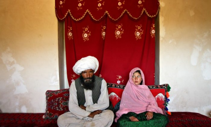 Ghulam, age 11, and Faiz, age 40, sit for a portrait in her home prior to their wedding in Afghanistan. According to the women's ministry and women's NGOs, approximately 57 percent of Afghan girls get married before the legal age of 16. Once the girl's father has agreed to the engagement, she is pulled out of school immediately. (Stephanie Sinclair/VII)
