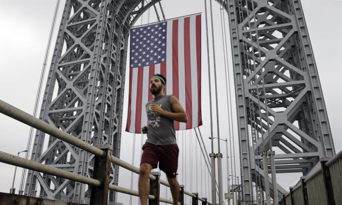 A runner passes under the largest free-flying American flag in the world over the George Washington Bridge Monday, Sept. 2, 2013, in Fort Lee, N.J. The flag flew on Labor Day under the upper arch of the bridge's New Jersey tower. (AP Photo/Mel Evans)