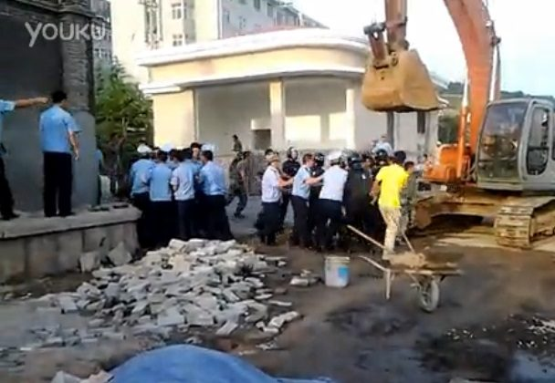Urban enforcement officials, or chengguan, face off against People's Liberation Army soldiers during a recent clash in Shandong Province. The chengguan overcame the PLA to demolish a structure that had been deemed illegal. (Molihua.org)