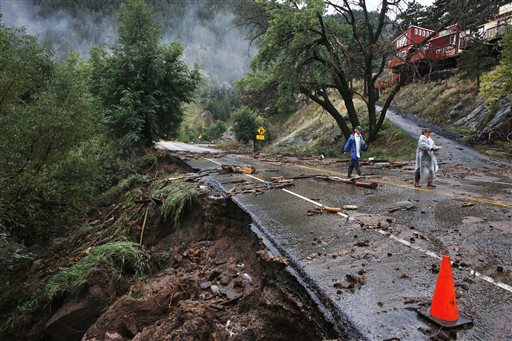 Brother and sister Patrick Tinsley and Mary Kerns walk into Boulder, Colo., from their mountain community Magnolia, where road access is shut off by debris from days of record rain and flooding, at the base of Boulder Canyon, Colo., Friday, Sept. 13, 2013. (AP Photo/Brennan Linsley)