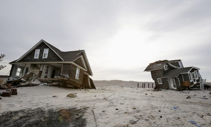 This Feb. 22,2013 file photo shows Two heavily damaged homes on the beach in Mantoloking, N.J., from Superstorm Sandy. Man-made global warming may decrease the likelihood of the already unusual steering currents that pushed Superstorm Sandy due west into New Jersey in a freak 1-in-700 year path, researchers report. While that may sound like the rare good climate change news, it's probably not, according to the study's authors, because they only looked at steering currents and other factors, including stronger storms, and sea level rise can and likely will outweigh any benefit from changing air patterns. The study is disputed by other scientists who have been vocal about the meteorological factors behind Sandy. (AP Photo/Mel Evans, File)