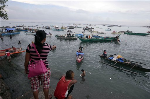 Villagers arrive by boats to flee the current standoff between Government troopers and Muslim rebels at the southern port city of Zamboanga in southern Philippines Wednesday, Sept. 11, 2013. Muslim rebels holding scores of hostages in the southern Philippines are demanding international mediation, an official said Wednesday, as fresh rounds of fire broke out between government troops and the guerrillas on the third day of the standoff. The rebels, enraged by a broken peace deal with the government, are holding the civilian hostages as human shields near the port city of Zamboanga. Troops have surrounded the Moro National Liberation Front guerrillas and their hostages in four coastal villages. (AP Photo/Bullit Marquez)