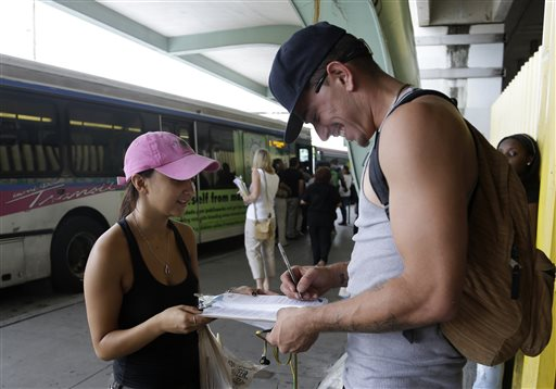 With Obamacare set to start soon, people are wondering about exemptions. Here, Maygan Rollins, 22, a field organizer with Enroll America, left, talks with Jerry Correa, 27, right, about his health care options while canvassing at a bus stop, Wednesday, Sept. 25, 2013, in Miami. (AP Photo/Lynne Sladky)