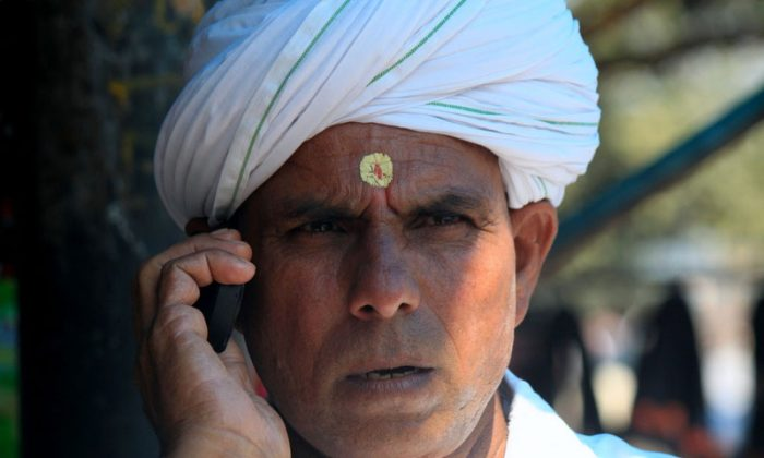 An Indian man talks on his mobile phone in the pilgrim town of Haridwar in Uttrakhand state of India on 11 October 2012. A recent study by research firm Juxt indicated that about 554 million people in Indian own mobile phones. (VENUS UPADHAYAYA/EPOCH TIMES)
