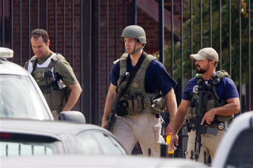 In this file photo from 2013, armed U.S. Marshals leave the scene where a gunman was reported at the Washington Navy Yard in Washington. (AP Photo/Jacquelyn Martin)