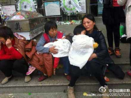 Relatives hold the deceased mother's two other children as they wait in front of the hospital. (Weibo.com)