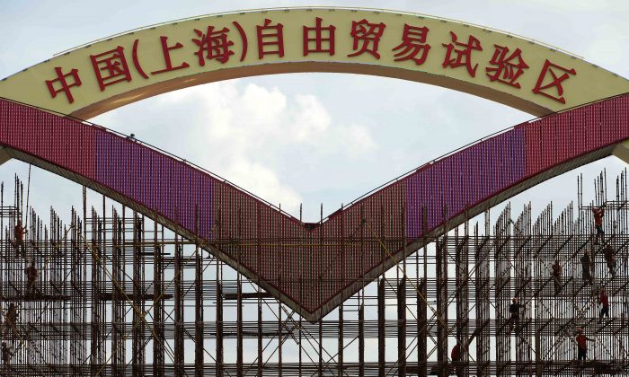 This picture taken on Sept. 23, 2013 shows laborers working on a large sign reading 'China (Shanghai) Pilot Free Trade Zone' on a gate of Shanghai Waigaoqiao Free Trade Zone (FTZ), before its formal launch in September 29. The free convertibility of the yuan inside the FTZ may trigger a wave of corruption and rent seeking by Chinese regime officials, argues Frank Xie. (STR/AFP/Getty Images)